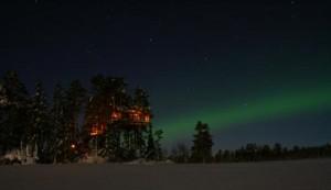 Stjerneklar vinternatt med striper av nordlys over ei av tretopphyttene 19.2.14. Foto tretopphytter.no